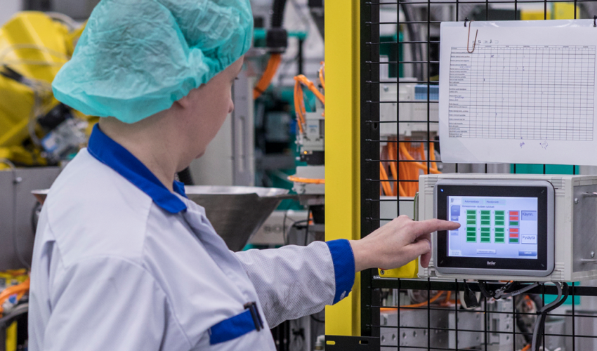 Staff member adjusting an automated production unit